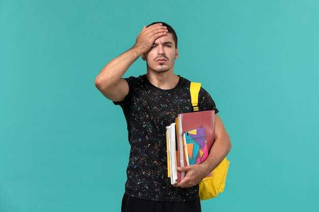 Front view of male student in dark t-shirt yellow backpack holding copybook and files on the blue wall