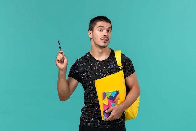 Vista frontale dell'allievo maschio nello zaino giallo della maglietta scura che tiene la penna e gli archivi del quaderno sulla parete blu-chiaro