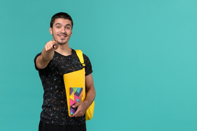 Front view of male student in dark t-shirt yellow backpack holding copybook pen and files on the light-blue wall
