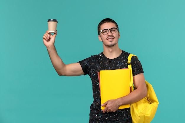 Vista frontale dello studente maschio in zaino giallo t-shirt scura che tiene diversi file e caffè sulla parete blu