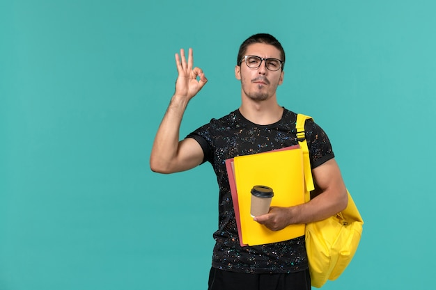 Front view of male student in dark t-shirt yellow backpack holding different files and coffee on blue wall
