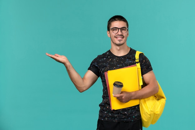 Front view of male student in dark t-shirt yellow backpack holding different files and coffee smiling on blue wall