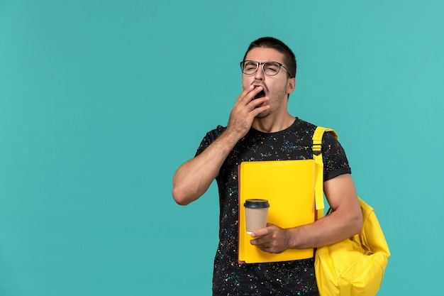 Front view of male student in dark t-shirt yellow backpack holding different files and coffee yawning on blue wall