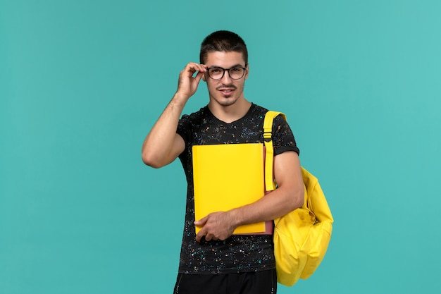 Front view of male student in dark t-shirt yellow backpack holding different files on light-blue wall