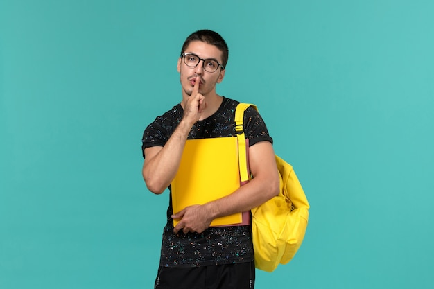 Front view of male student in dark t-shirt yellow backpack holding different files on light blue wall