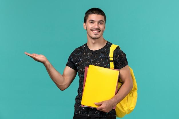 Vista frontale dello studente maschio in zaino giallo t-shirt scura che tiene diversi file sulla parete blu chiaro