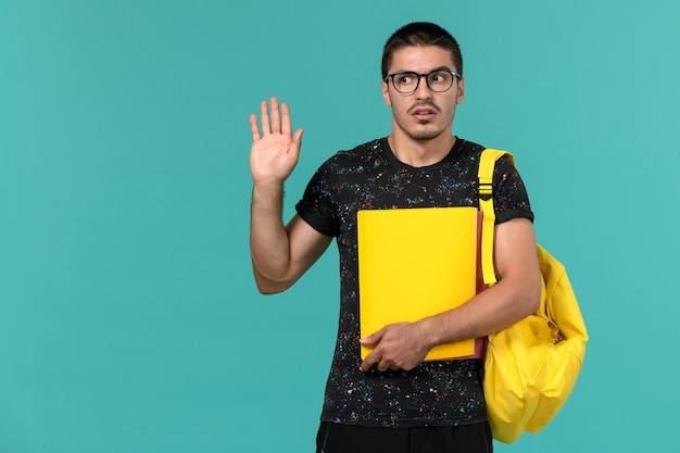 Front view of male student in dark t-shirt yellow backpack holding different files on the light-blue wall