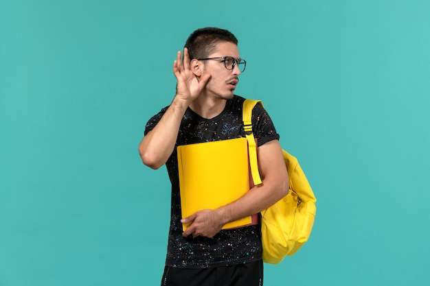 Front view of male student in dark t-shirt yellow backpack holding different files trying to hear on light blue wall