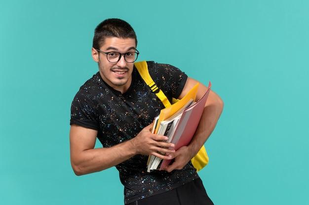 Vista frontale dell'allievo maschio nello zaino giallo della maglietta scura che tiene file e libri sulla parete azzurra