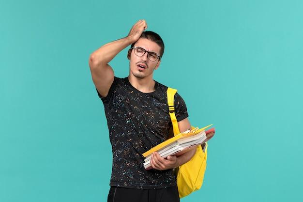 Vista frontale dell'allievo maschio nello zaino giallo della maglietta scura che tiene file e libri pensando sulla parete blu