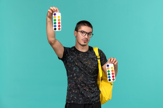 Front view of male student in dark t-shirt yellow backpack holding paints on the blue wall