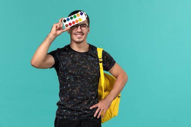 Vista frontale dello studente maschio in t-shirt scura zaino giallo che tiene vernici sorridente sulla parete blu