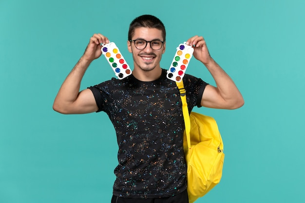 Front view of male student in dark t-shirt yellow backpack holding paints smiling on blue wall