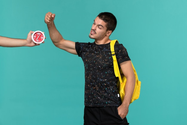 Front view of male student in dark t-shirt yellow backpack looking at clocks on light blue wall