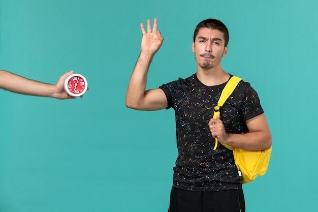 Vista frontale dello studente maschio in zaino giallo t-shirt scura in posa sulla parete blu chiaro
