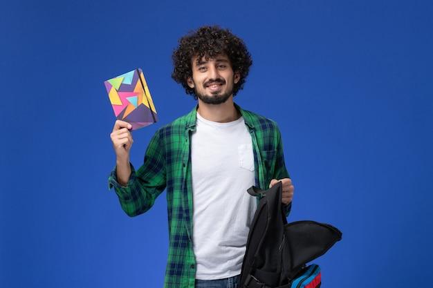 Vista frontale dello studente maschio in camicia a scacchi verde che tiene zaino nero e quaderno sulla parete azzurra
