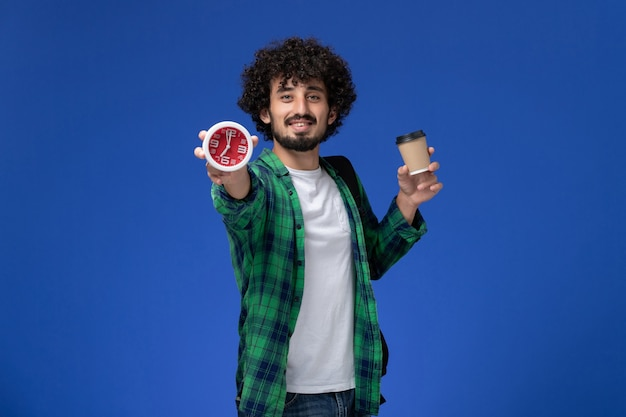 Front view of male student in green checkered shirt wearing black backpack and holding clocks and coffee on blue wall