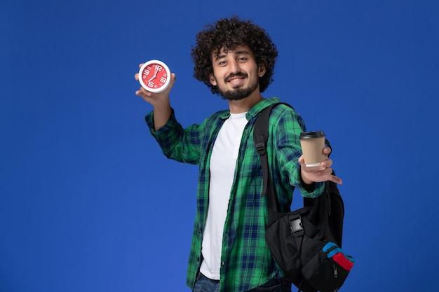 Vista frontale dello studente maschio in camicia a scacchi verde che porta zaino nero e che tiene orologi e caffè sulla parete blu