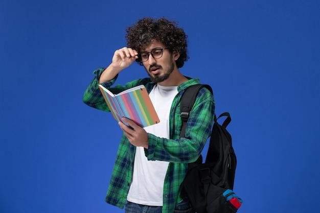 Vista frontale dello studente maschio in camicia a scacchi verde che porta zaino nero e che tiene la lettura del quaderno sulla parete blu