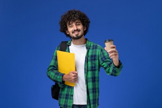 Vista frontale dello studente maschio in camicia a scacchi verde che porta zaino nero e che tiene file e caffè sulla parete blu