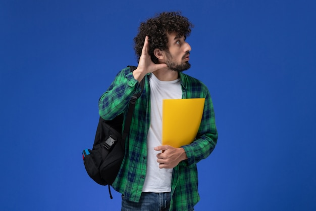 Front view of male student in green checkered shirt wearing black backpack and holding files trying to hear on blue wall