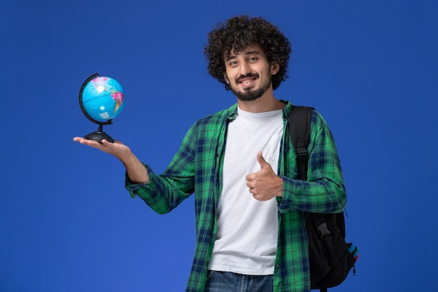 Front view of male student in green checkered shirt wearing black backpack and holding little globe on blue wall