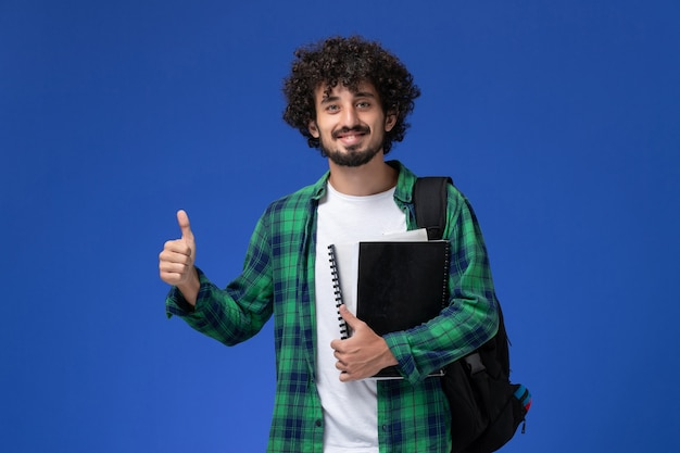 Front view of male student in green checkered shirt with black backpack holding copybooks smiling on blue wall