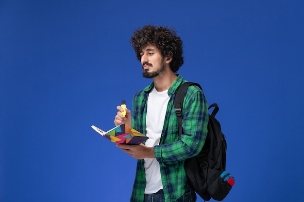 Front view of male student in green checkered shirt with black backpack holding felt pen and copybook on blue wall