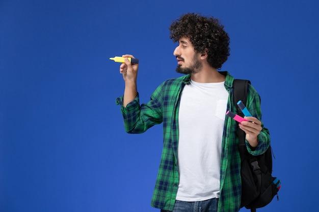 Vista frontale dello studente maschio in camicia a scacchi verde con zaino nero che tiene i pennarelli sulla parete blu