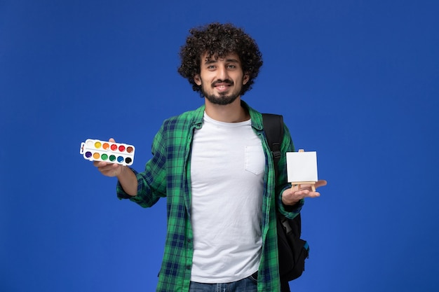 Front view of male student in green checkered shirt with black backpack holding paints and easel on blue wall