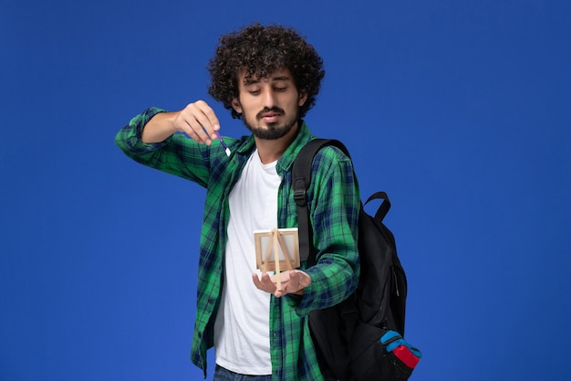 Front view of male student in green checkered shirt with black backpack holding tassel and easel on blue wall