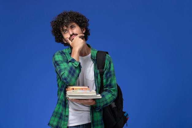 Front view of male student in green checkered shirt with black backpack thinking holding copybooks and files on blue wall