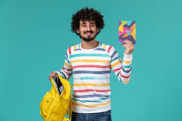 Vista frontale dello studente maschio che tiene zaino e quaderno gialli sulla parete blu