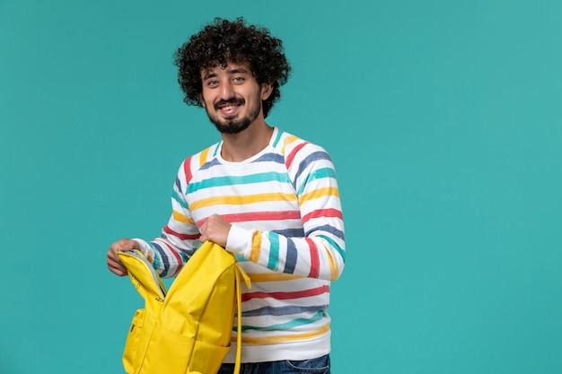 Vista frontale dello studente maschio che tiene zaino giallo e quaderno sorridente sulla parete blu