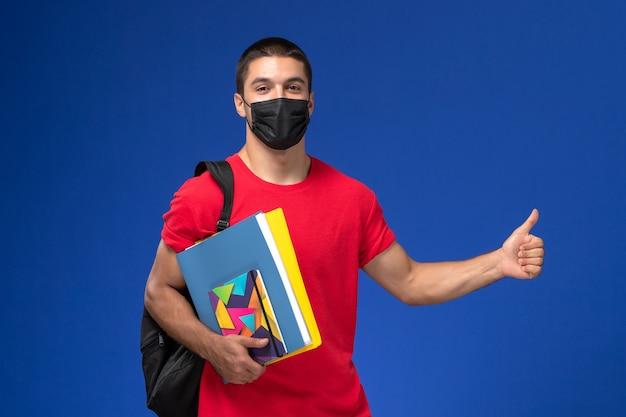 青い背景にコピーブックを保持している黒い滅菌マスクのバックパックを身に着けている赤いtシャツの正面図男子学生。