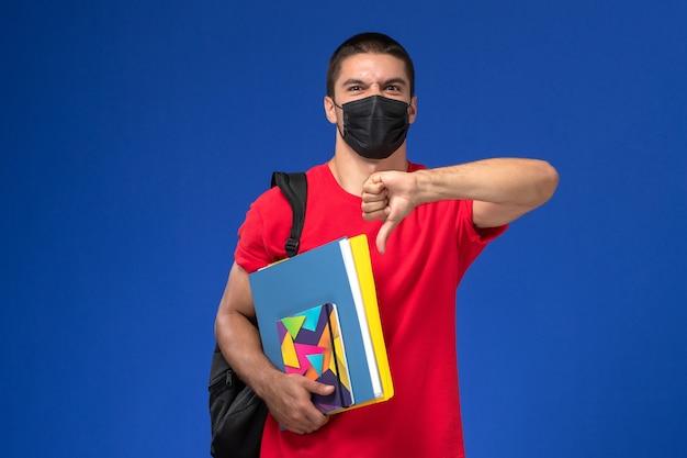 青い背景のサインとは異なり、コピーブックを保持している黒い滅菌マスクのバックパックを身に着けている赤いtシャツの正面図の男子生徒。