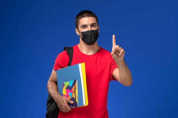 青い背景に上げられた指でファイルを保持している黒い滅菌マスクのバックパックを身に着けている赤いtシャツの正面図の男子生徒。