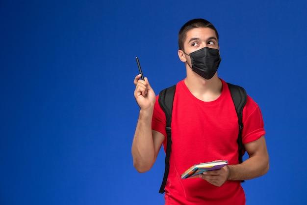 파란색 배경에 펜과 카피 북을 들고 검은 살 균 마스크에 배낭을 착용하는 빨간 티셔츠에 전면보기 남성 학생.