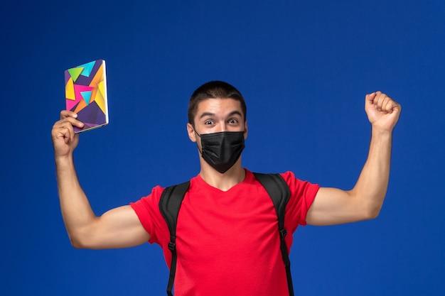 파란색 배경에 기쁨 펜과 카피 북을 들고 검은 살 균 마스크에 배낭을 착용하는 빨간 티셔츠에 전면보기 남성 학생.