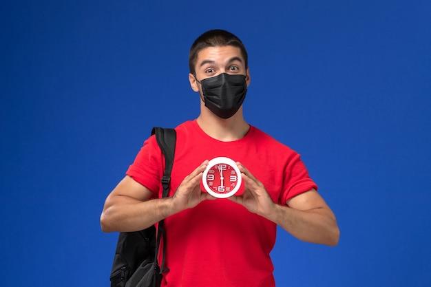 青い背景に時計を保持しているマスクとバックパックを身に着けている赤いtシャツの正面図の男子生徒。