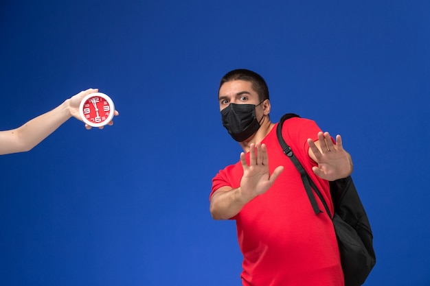 青い机の上に時計が怖いマスクとバックパックを身に着けている赤いtシャツの正面図の男子生徒。