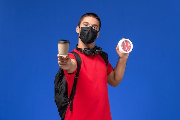 水色の背景に時計のコーヒーを保持しているバックパックとマスクを身に着けている赤いtシャツの正面図の男子生徒。