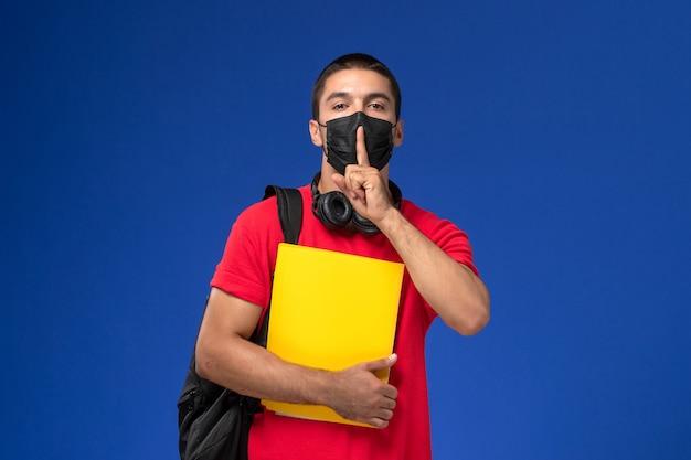 青い背景に黄色のファイルを保持しているバックパックとマスクを身に着けている赤いtシャツの正面図男子学生。