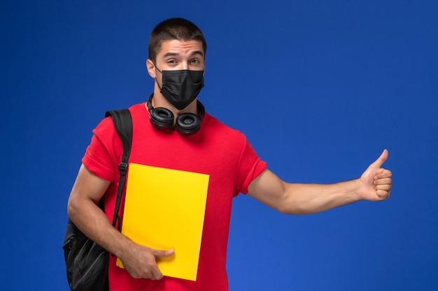青い机の上に黄色のファイルを保持しているバックパックとマスクを身に着けている赤いtシャツの正面図の男子生徒。