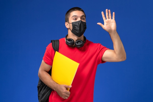 파란색 바탕에 노란색 파일을 들고 배낭 마스크를 쓰고 빨간 티셔츠에 전면보기 남성 학생.
