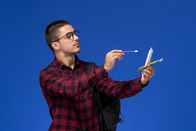 Front view of male student in red checkered shirt with backpack drawing with tassel on blue wall