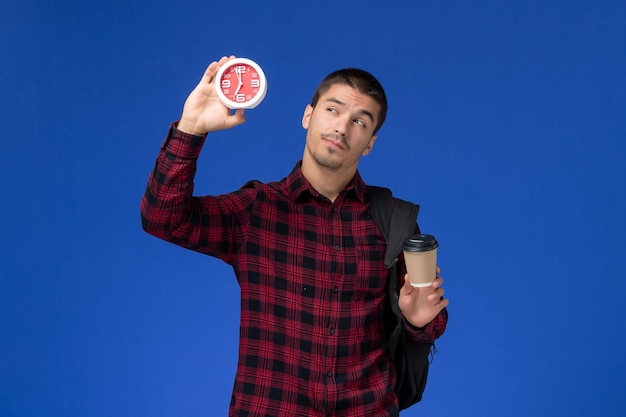Vista frontale dello studente maschio in camicia a scacchi rossa con lo zaino che tiene gli orologi e il caffè sulla parete blu
