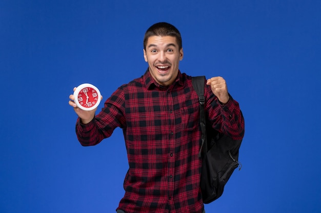 Front view of male student in red checkered shirt with backpack holding clocks and rejoicing on blue wall
