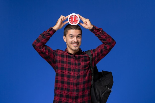 Front view of male student in red checkered shirt with backpack holding clocks and smiling on blue wall