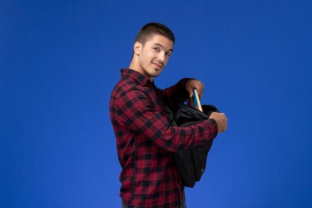 Vista frontale dello studente maschio in camicia a scacchi rossa con zaino che tiene il quaderno sulla parete blu
